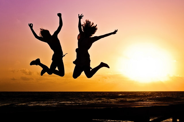 2 women jumping in sunset