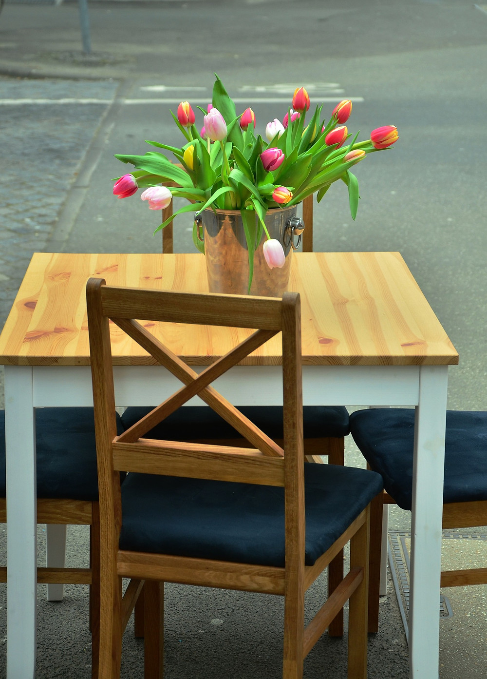 a chair at a table with a vase of tulips