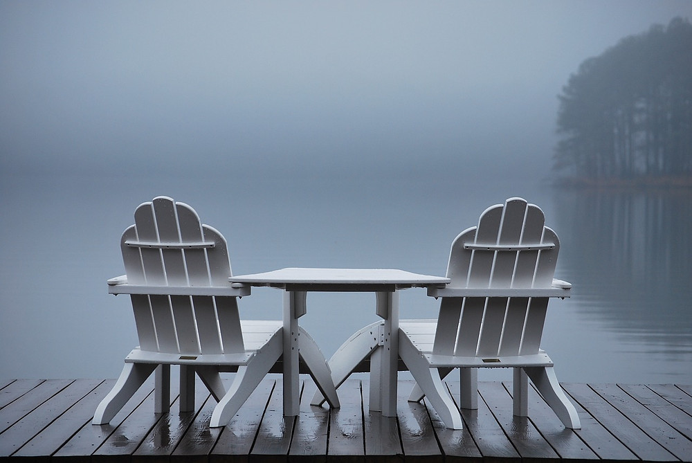 chairs by a foggy lake