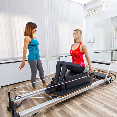 Woman exercising on Pilates reformer wit