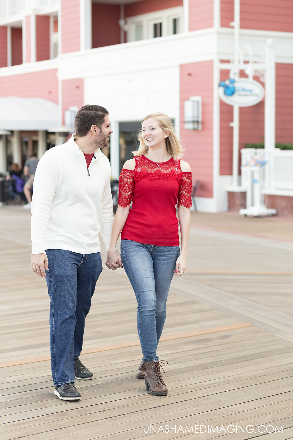 Disney Boardwalk Engagement Session: Megan & Ryan. Girl in red shirt and jeans holding hands.
