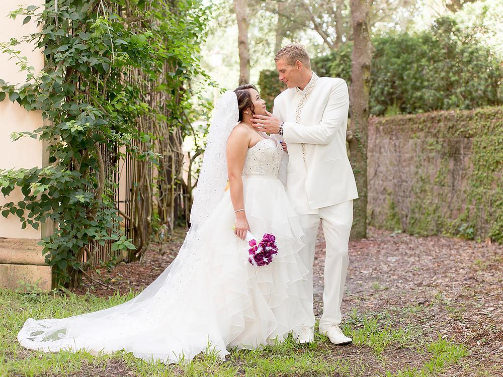 Groom holds brides face at wedding. Wedding couple in orlando florida at crystal ballroom veranda.