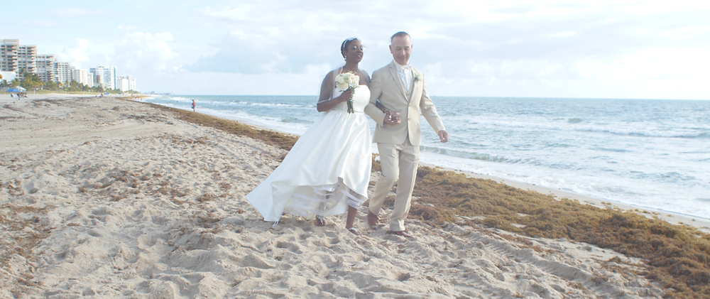 Couple exchanging wedding vows on the beach while walking on the beach.