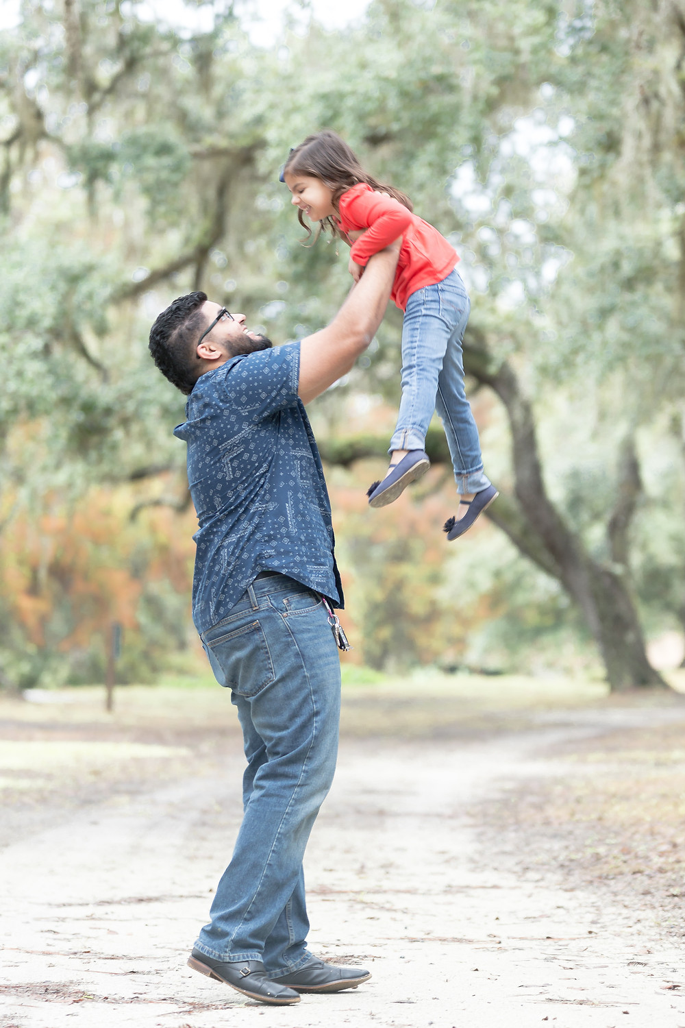 Father throws daughter in the air.
