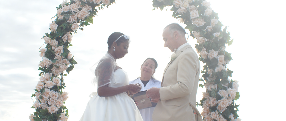 Couple exchanging wedding vows on the beach in front of a floral arch.