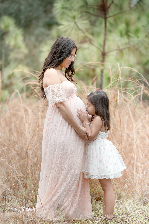 Little girl kisses her mother's pregnant belly.