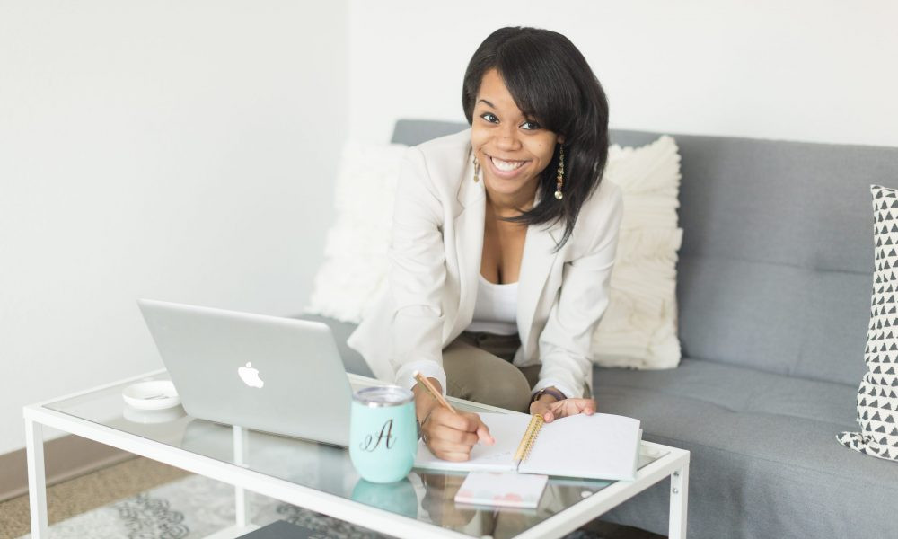 VoyageMIA Features Anesha Collins, African American female sitting on couch with a computer smiling.