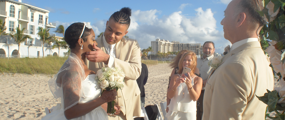 Son wipes tears off the face of his mother as Couple exchanging wedding vows on the beach in front of a floral arch.