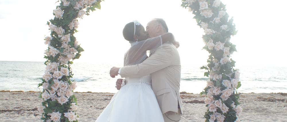 Couple kissing on the beach in front of a floral arch.