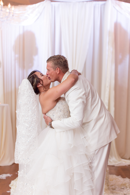 Bride kissing husband in minerva bridal gown. Wedding couple in orlando florida at crystal ballroom veranda.