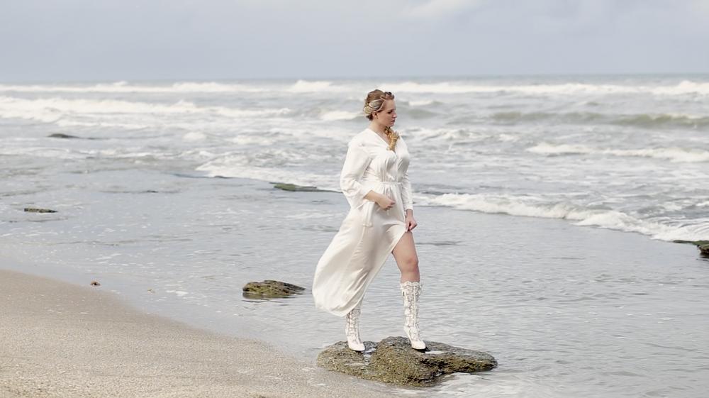 Woman on beach in robe, sand, love. love, bride looking at husband, blonde hair, weddings.