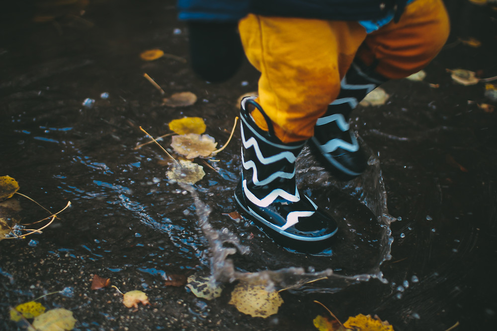 Boy in gumbootes jumping into a puddle
