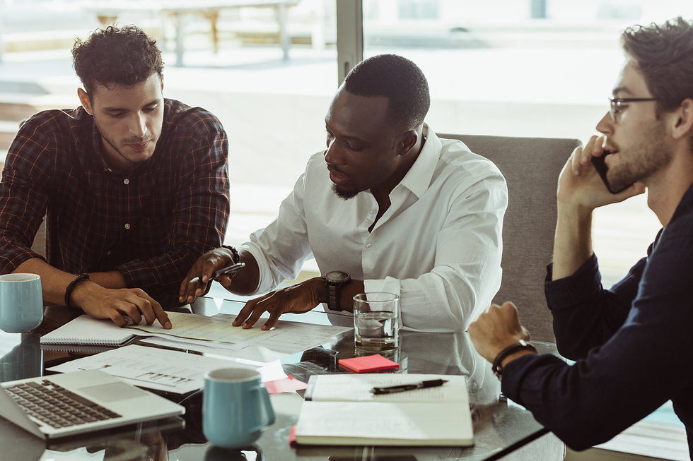 Businessmen discussing work sitting at conference table in office. Two men discussing work