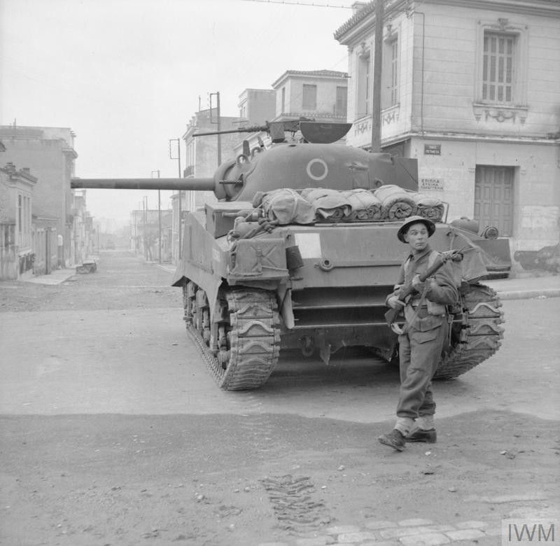 A rifleman acts as 'tail-end Charlie', guarding the commander of a Sherman tank from snipers during operations against ELAS in Athens, 18 December 1944. (Source: © IWM (NA 20934))