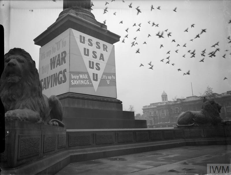 A striking photograph of War Savings posters around the base of Nelson's Column, Trafalgar Square. The lions at the base of the Column can also be seen, as can a flock of pigeons, flying overhead. The poster tells citizens 'It's up to 'U' to buy War Savings'. (Source: © IWM (D 5598))