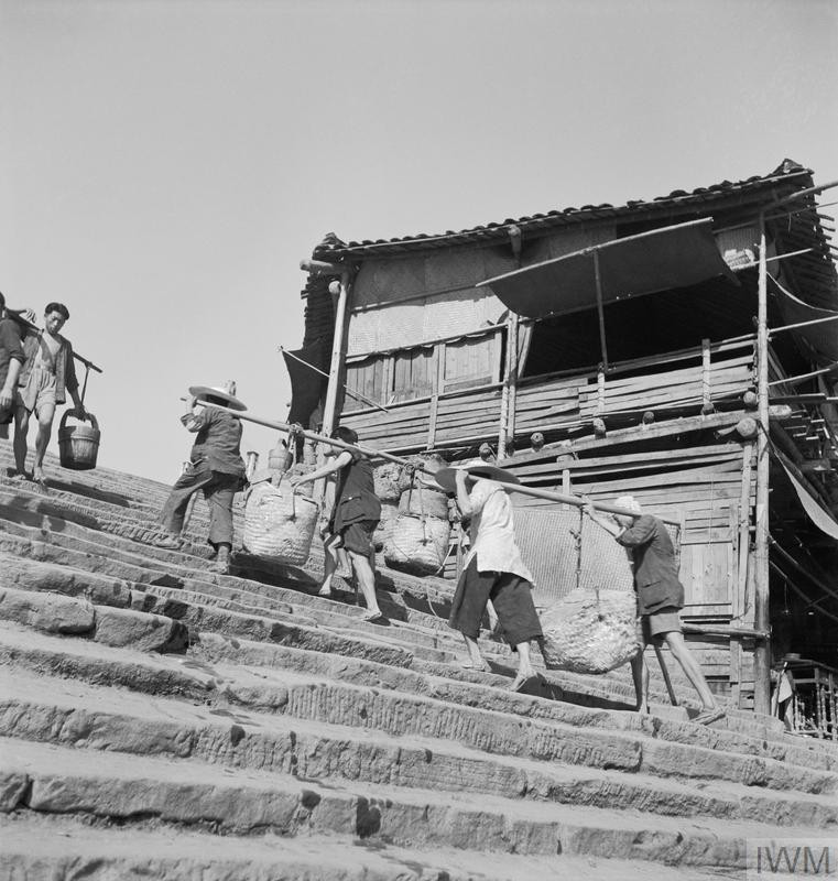 Four coolies carry their loads on a single pole up the wharfside steps at Chungking, c. 1944. (Source: © IWM (IB 3121C))