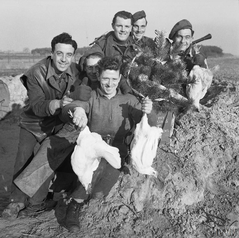 A group of cheerful men from the Royal Artillery display chickens acquired for their Christmas dinner, Venray in Holland, 24 December 1944. (Source: © IWM (B 13093))