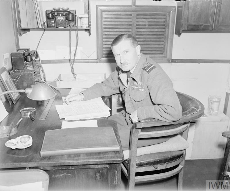 Air Vice-Marshal Robert Foster, Air Officer Commanding the Desert Air Force, sitting in his office trailer at DAF Advanced Headquarters at Cesena, Italy. (Source: © IWM (CNA 3338))