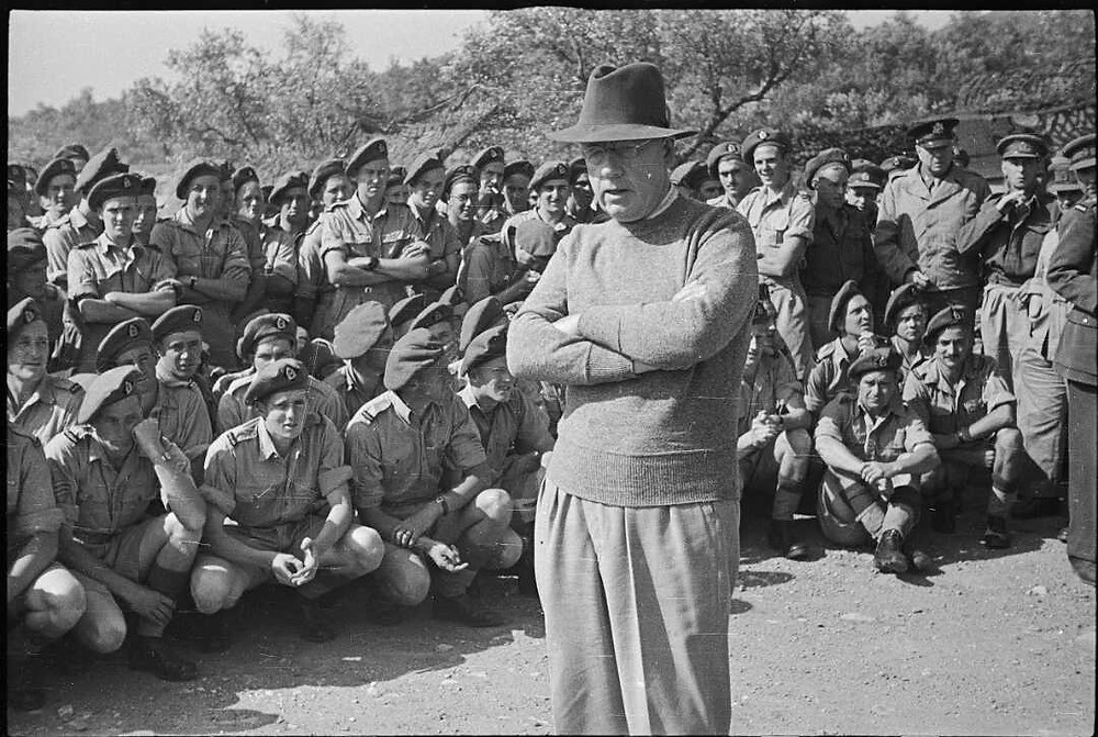 Prime Minister Peter Fraser standing in front of a group of soldiers from the Sixth New Zealand Infantry Brigade, while visiting New Zealand troops in the Cassino area, Italy. Photograph taken circa 28 May 1944 by George Robert Bull. (Source: National Library of New Zealand)