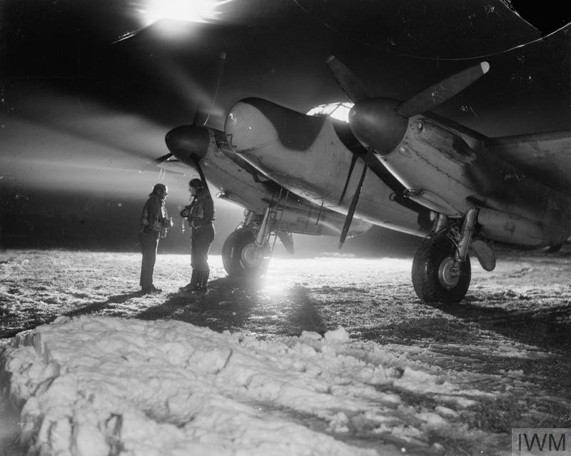 Warrant Officer D Gosling (left) and Squadron Leader G H Hayhurst of No. 604 Squadron RAF, stand in front of their De Havilland Mosquito NF Mark XII in the snow at B51/Lille-Vendeville, France, before taking off on a night-fighter sortie. (Source: © IWM (CL 1827))