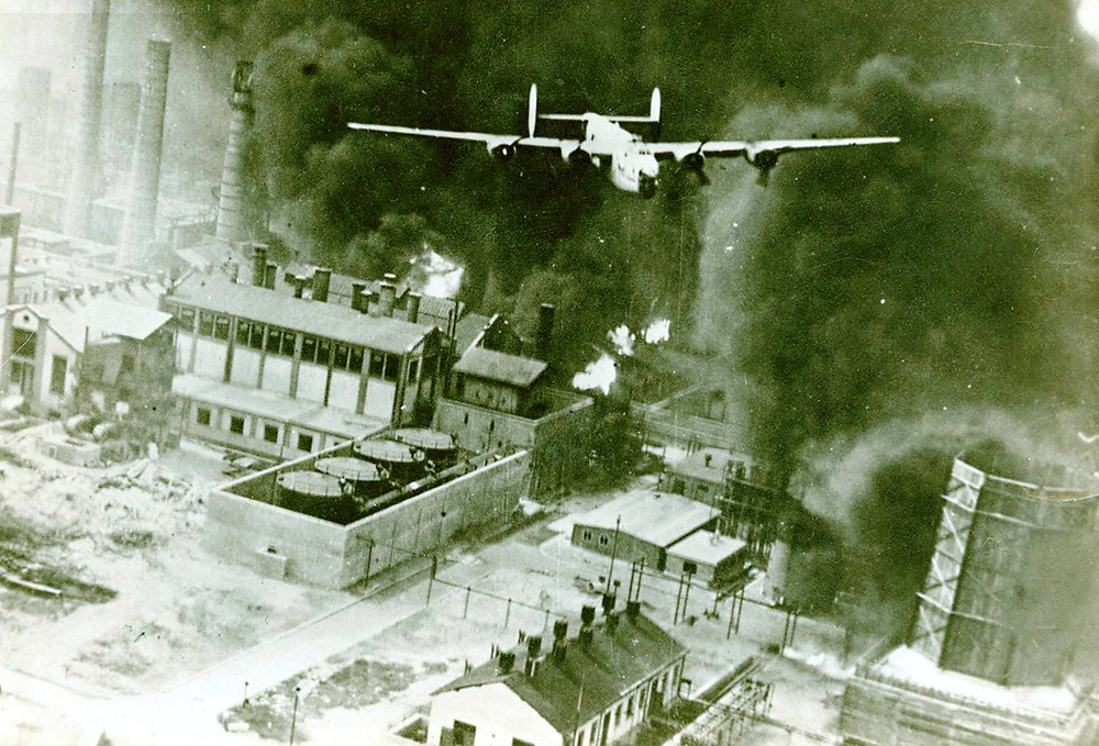 A B-24D Liberator flying over a burning oil refinery at Ploesti, Rumania, 1 August 1943. (Source: © IWM (UPL 15565))