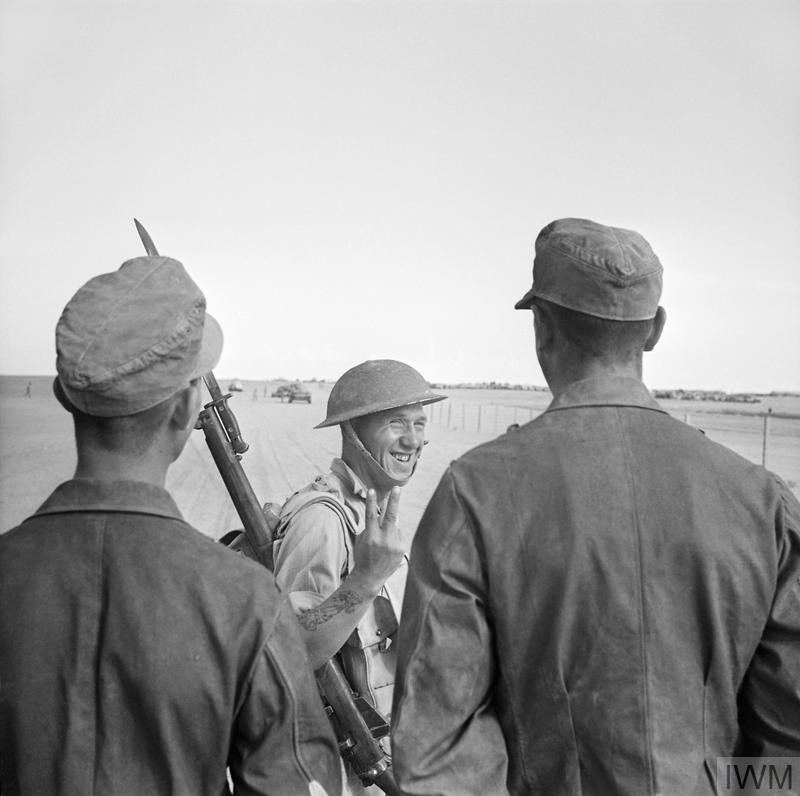 A British soldier gives a V-for-Victory sign to German prisoners captured at El Alamein, 26 October 1942. (Source: © IWM (E 18522))