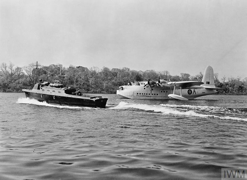 A peaceful scene at Castle Archdale (formerly Logh Erne) in Northern Ireland on 20 May 1943, as a seaplane tender passes a Sunderland of No 201 Squadron. The censor has removed all trace of the aircraft's fuselage-mounted ASV aerials. (Source: © IWM (CH 11075))