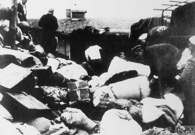 "Transport of Jewish Hungarians arriving at Auschwitz II-Birkenau camp, c.June 1944: deportees' property being unloaded from trucks and sorted by prisoners at the warehouses of ""Canada I"" near Auschwitz I. (Source: © IWM (HU 97046))"