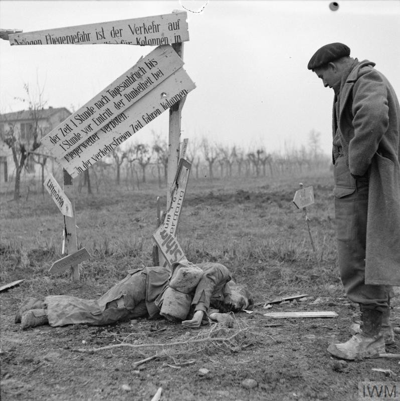 A soldier of 2nd New Zealand Division looks at a dead German at the foot of a smashed road sign at Celle, near Faenza, 20 December 1944. (Source: © IWM (NA 20879))