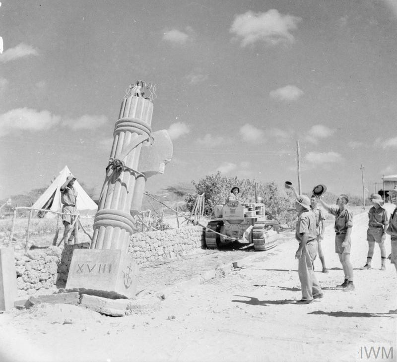 British troops use a bulldozer to pull down a fascist stone monument at Kismayu in Italian Somaliland, 11 April 1941. (Source: © IWM (E 2367))
