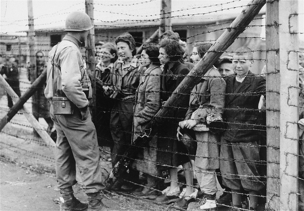 Women and children survivors in Mauthausen speak to an American liberator through a barbed wire fence, May 1945. (Source: United States Holocaust Memorial Museum, courtesy of Col. P. Richard Seibel)