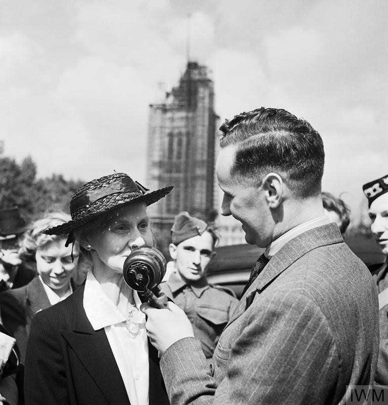 As part of a programme entitled 'Meet John Londoner', here we see Mrs Galraith, a member of the public, answering a question posed by correspondent Wynford Vaughan Thomas. Mrs Galraith's face is partly obscured by the microphone held by Vaughan Thomas. The interview is taking place in a sunny Victoria Gardens on Victoria Embankment and behind them, part of the Houses of Parliament can be seen, covered in scaffolding. This photograph was probably taken in September 1941. (Source: © IWM (D 4577))
