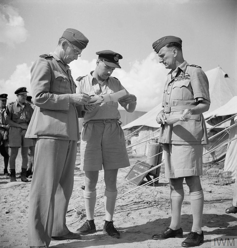 Air Chief Marshal Sir Arthur Tedder, Air Officer Commanding-in-Chief, Middle East (left), studies photographs taken during operations by No. 252 Squadron RAF being shown to him by the Commanding Officer, Wing Commander P H Bragg at Idku, Egypt, during Tedder's extended visit to the Western Desert Air Force and No. 201 Group units prior to the Alamein offensive. Air Vice-Marshal L H Slatter, Air Officer Commanding No. 201 (Naval Co-operation) Group RAF, looks on at right. (Source: © IWM (CM 3747))