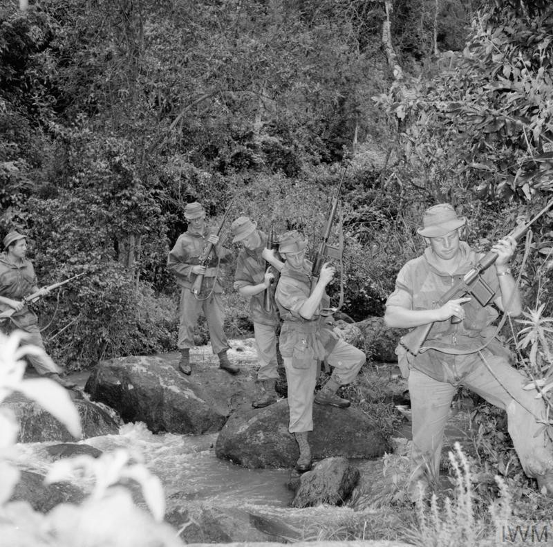 British Army patrol crossing a stream. The soldiers carry a variety of weapons, including the 7.62 mm X8E1 Self Loading Rifle (1st and 2nd soldiers from right); the 9 mm Sten Mk5 (3rd soldier); and the Lee Enfield .303 Rifle No. 5 (4th and 5th soldiers). (Source: © IWM (MAU 587))