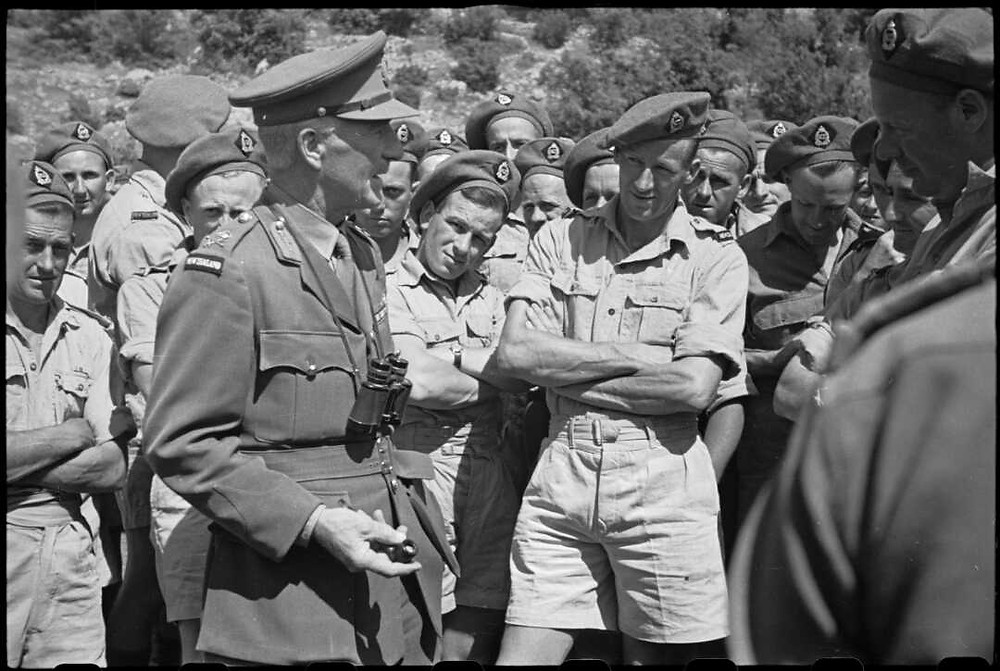 Lieutenant General Edward Puttick, who accompanied Prime Minister Peter Fraser, talks with men of the NZ Divisional Supply Company and men of the Divisional Petrol Company in the Volturno Valley area in Italy, during World War II. Photograph taken circa 30 May 1944 by George Robert Bull. (Source: National Library of New Zealand)
