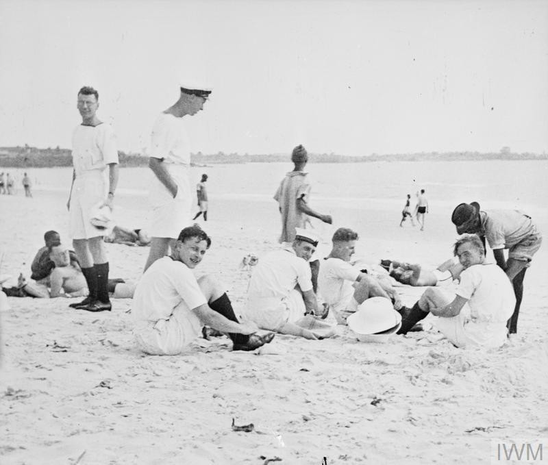 Royal Navy ratings on the ready to leave Lumley Beach outside of Freetown, Sierra Leone. Penny-a-time native boys are busy rinsing costumes and feet. (Source: © IWM (A 8800))