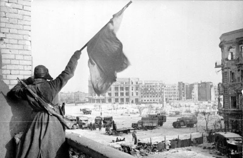 A Soviet soldier waving the Red Banner over the central plaza of Stalingrad in 1943 (Source: Wikimedia)