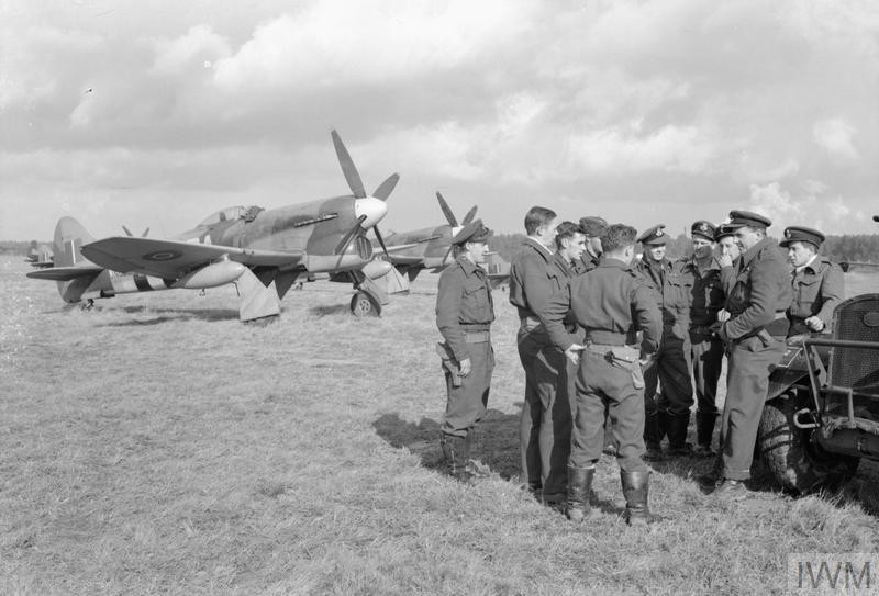 Pilots of No 486 Squadron, Royal New Zealand Air Force, assemble in front of their Hawker Tempest fighter-bombers on an airfield in Belgium. No 486 was one of three New Zealand squadrons in 2nd Tactical Air Force, supporting the Allied armies in North-West Europe. (Source: © IWM (CL 1382))