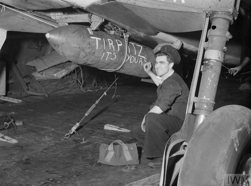 A sailor aboard HMS Furious chalks a message on a bomb slung beneath an aircraft due to take part in the attack on the Tirpitz in Alten Fjord, Norway, 3 April 1944. (Source: © IWM (A 22640))