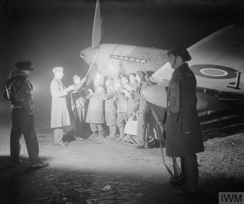 An aircrew officer and a guard on night duty listen to a choir, composed of the ground crew of No. 122 Wing, singing Christmas carols by a Hawker Tempest in a dispersal at Volkel airfield (B80), Holland, conducted by the Wing's Padre, Squadron Leader K J Morgan. (Source: © IWM (CL 1736))