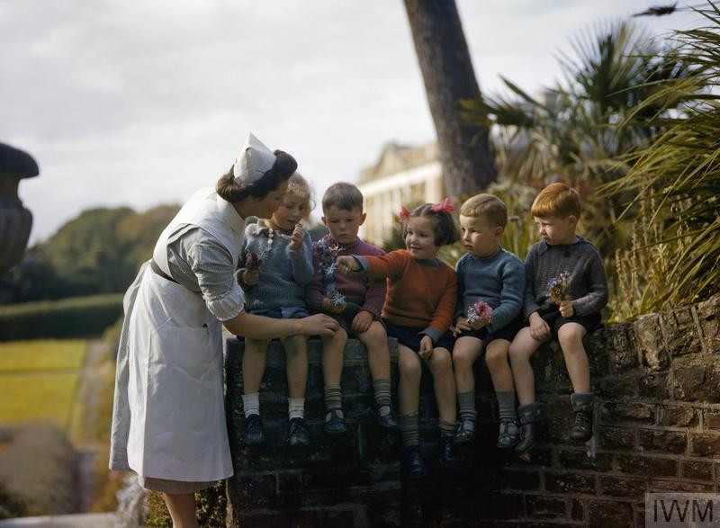 A nurse with young child evacuees in the gardens of Tapeley Park, at Instow in North Devon, October 1942. The house was used to accommodate 50 children evacuated from Plymouth after a series of Luftwaffe bombing attacks in March and April 1941. (Source: © IWM (TR 248))