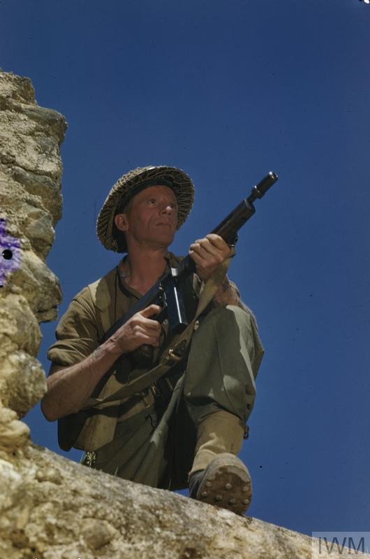 Corporal M Smith of the Duke of Cornwall's Light Infantry, posing with a tommy gun on the wall at the main Headquarters of the Eighth Army in the San Angelo area. Corporal Smith, a former metal polisher from Birmingham, served in North Africa and Egypt before going to Italy in early 1944. He was involved in the fighting north of Cassino and on the Garigliano River. (Source: © IWM (TR 1710))