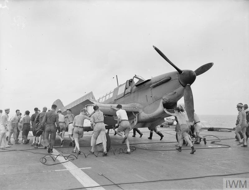 A Fairey Fulmar, with wings folded being wheeled to the lift on the deck of HMS Formidable during the invasion of Madagascar, c. 1942 (Source: © IWM (A 9069))