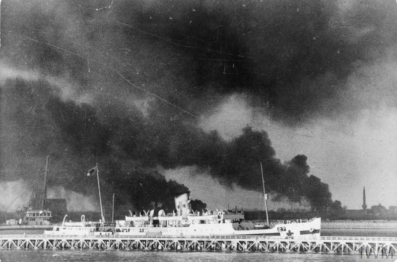 A hospital ship carrying wounded soldiers away from Dunkirk. In the background can be seen columns of smoke and flames from fires burning in the bomb and shell shattered port. (Source: © IWM (HU 73187))