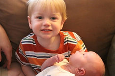 Newborn being held by his proud big brother, black and white image