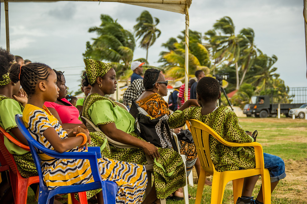 A Garifuna family spectates a series of speeches to celebrate their settlement in Belize and the conservation of their culture. Their colorful outfits remind one of West Africa.