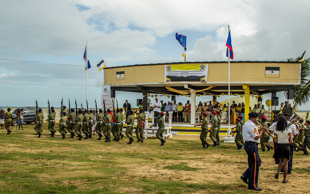 The Prime Minister of Belize, Dean Barrow, stands beneath a banner of Black, White, and Yellow as a small portion of his small army marches in celebration. This is Garifuna Settlement Day, this is a nation celebrating one of its diverse cultures as a collective -- political empowerment for cultural diversity.