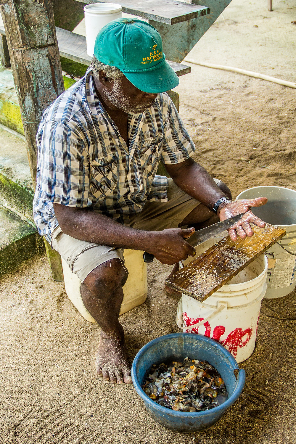Buck, a local fisherman on Tobacco Caye celebrates the completion of his mid-morning task, he just cleaned ~ 20 lbs of conch. Man living on the sea.