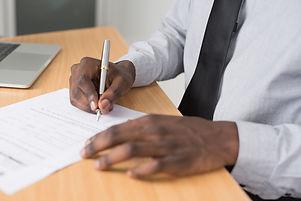 person-wearing-white-dress-shirt-signing