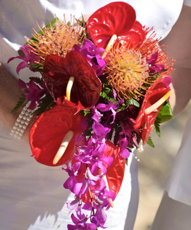 Red anthuriums, pincushion protea and purple orchid bouquet